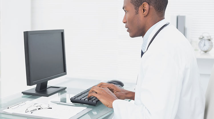 Doctor typing on computer