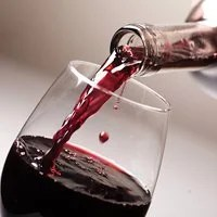 Wine from a wine bottle is being poured into a glass.