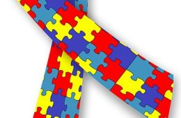 The image shown is the Autism awareness ribbon which features a multi colored jigsaw piece pattern.
