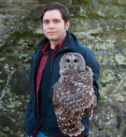 The image shows Fabian de Kok-Mercado, M.A., holds a barred owl..