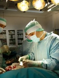 The image shows lead researcher Paolo Macciarini performing surgery.