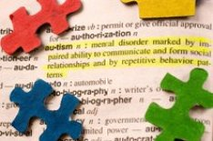 The image shows multi-colored jigsaw pieces around a dictionary definition of autism.