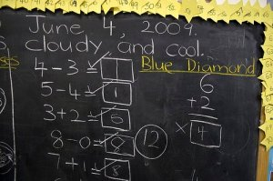 This image shows some basic math problems on a blackboard.