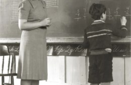 The image shows a teacher in the 1940's with a student.