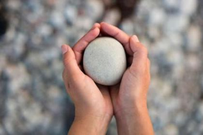 This image shows two hands holding a smooth looking rock.