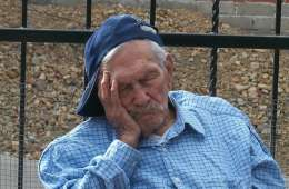 This image shows an old man sleeping on a park bench.