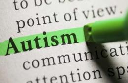 This image shows the word Autism in a dictionary. Someone is highlighting the word with a green highlighter pen.