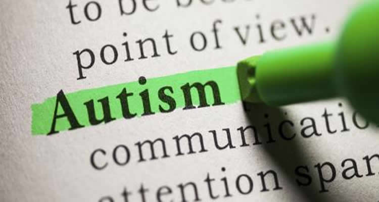 The image shows the word 'autism' highlighted in green in a dictionary.