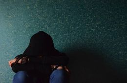 This image shows a girl sitting in the dark against a wall.