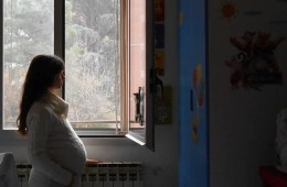 Images shows a pregnant woman looking out of a window.