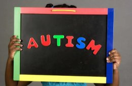 This shows a little girl holding up a blackboard with the word Autism written on it.