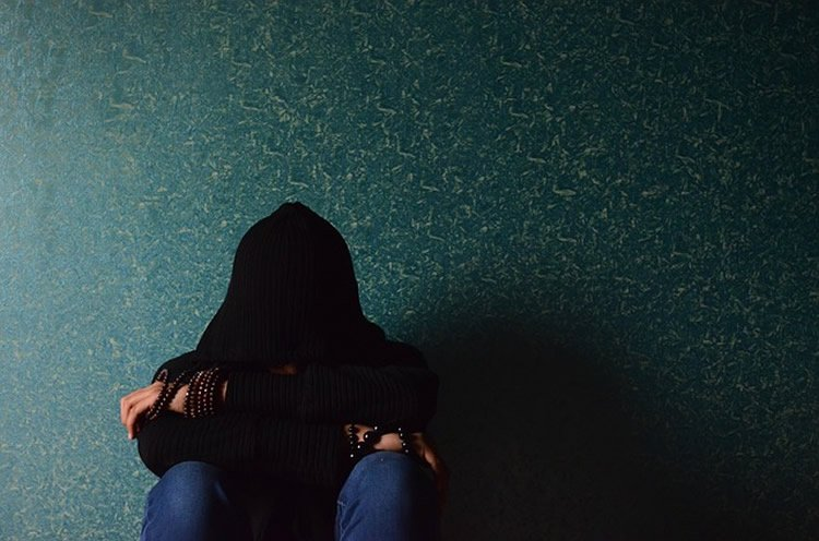 This shows a person in a hoodie curled up against a wall.