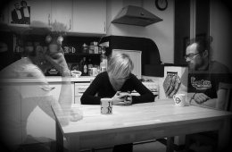 This image shows a woman sitting at a table. Next to her, faded out, are two men.