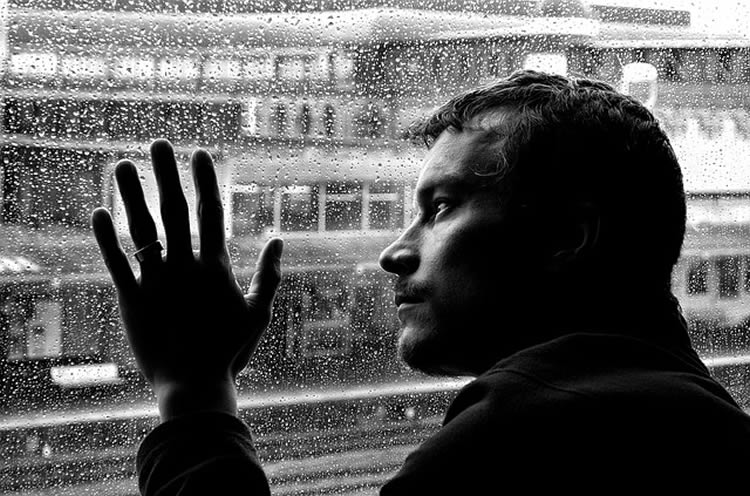 This image shows a man looking through a window. There is rain drops on the glass.