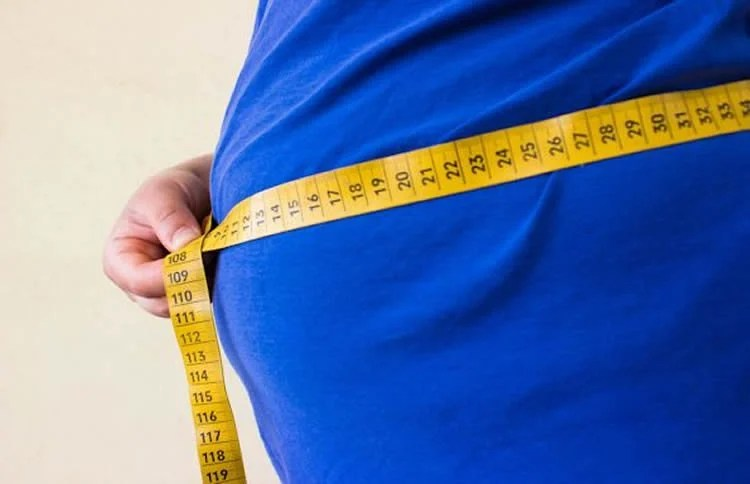This image shows an overweight man's tummy with a measuring tape around it.