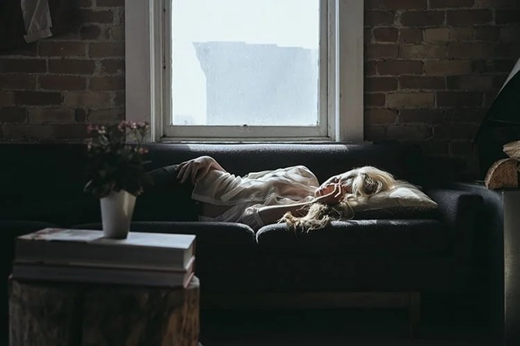 Image of a woman sleeping on a sofa.
