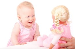 Image shows a baby looking at a doll.