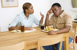 Image of a mom and son sitting at a table. The mom looks to be telling off the son, who has his head in his hands.