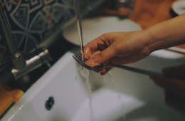 Photo of a person washing a fork.