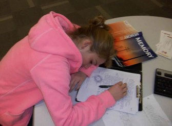 Photo of a girl sleeping on a school desk. Next to her is a memory text book.