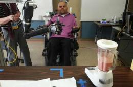 Image shows the patient gripping a drink with the robotic hand.
