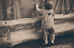 Photo of a toddler touching a wall.
