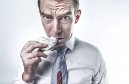 Image shows a man eating cake.