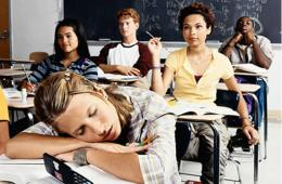 Image shows a teen girl sleeping at her school desk.