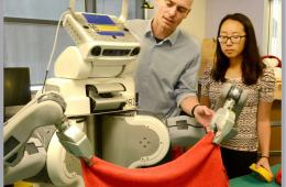 Image shows BRETT the robot folding a towel.
