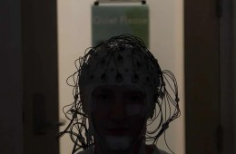 Image shows a person in an EEG helmet.