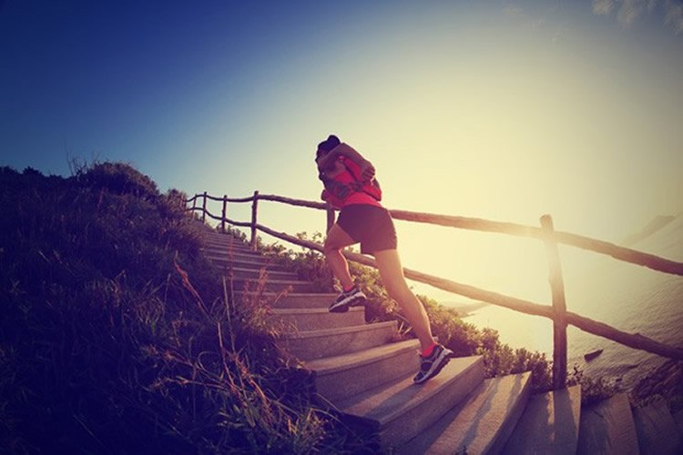 Image shows a woman running up steps on a beach.