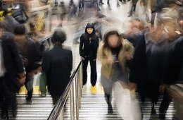 Image shows a woman walking up some steps.