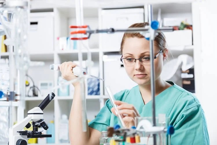 Image shows a woman performing an experiment in a lab setting.