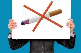 Image shows a person holding a no smoking sign.