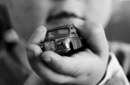 Image shows a little boy holding a toy car.