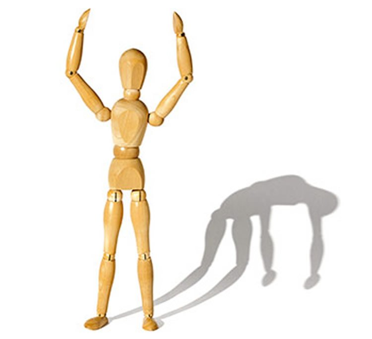 Image shows an artist wooden model standing with a shadow that is slumped over.