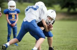 Image shows boys playing football.