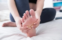 Image shows a person rubbing their foot.