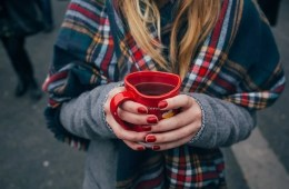 Image shows a woman holding a coffee cup.