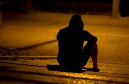 Image shows a depressed man sitting on a street in the dark.