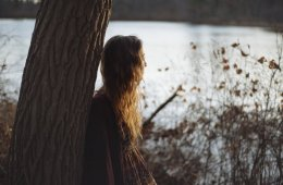 Image shows a woman sitting alone by a tree.