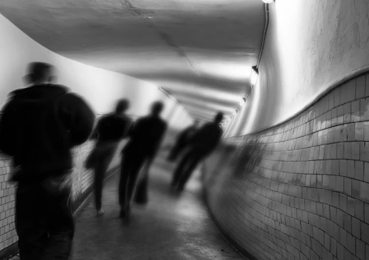 Image shows shadow people in a tunnel.