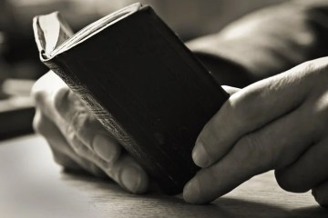 Image shows a book and a pair of old hands.
