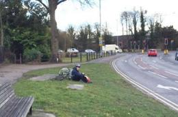 Image shows a person on the side of a road laying next to a bike.