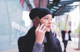 Image shows a woman talking on a phone.