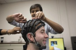 Image shows the researcher fitting an EEG helm onto a subject.
