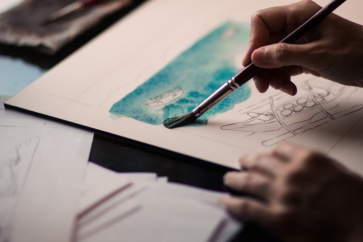 Image shows a person painting.