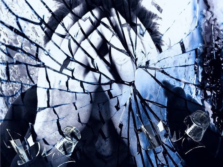 Image shows a cracked glass and a man looking as though he is in despair.