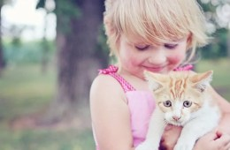 Image shows a girl hugging a cat.