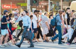 Image shows people walking in a crowd.